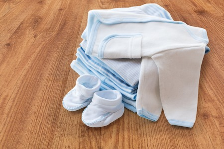 bootees: clothing, babyhood, motherhood and object concept - close up of white baby cardigan with bootees and pile of clothes for newborn boy on wooden table Stock Photo