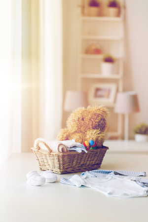 babyhood: babyhood, motherhood, clothing and object concept - close up of baby clothes and toys for newborn boy in basket at home Stock Photo