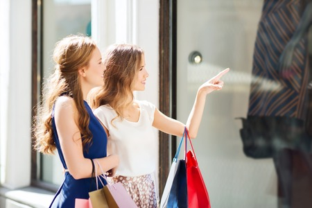 sale, consumerism and people concept - happy young women with shopping bags pointing finger to shop window in city Stock Photo