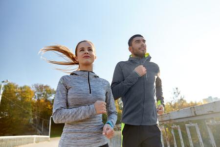 fitness, sport, mensen en levensstijlconcept - gelukkig paar dat in openlucht loopt