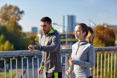 watch city: fitness, sport, people, technology and healthy lifestyle concept - smiling couple with heart-rate watch running over city highway bridge