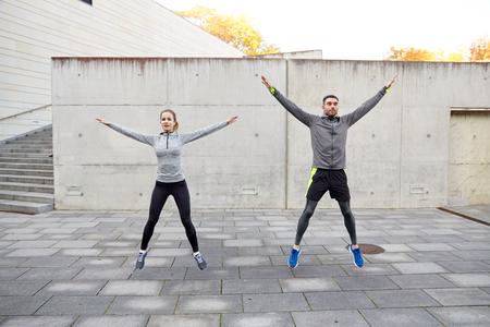 brincando: fitness, deporte, la gente, el ejercicio y el concepto de estilo de vida - el hombre y la mujer feliz haciendo jumping jack o ejercicio al aire libre salto estrellas Foto de archivo