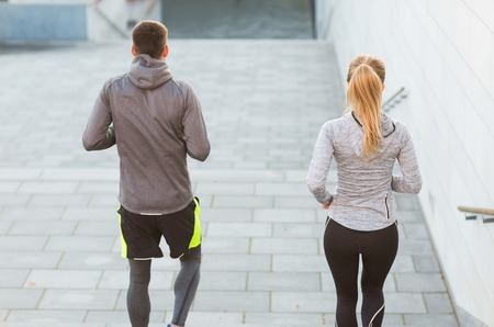 downstairs: fitness, sport, people, exercising and lifestyle concept - couple running downstairs on city stairs