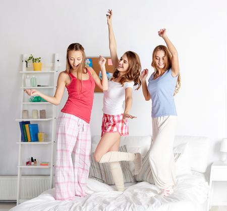 ragazze che ballano: amicizia, le persone e il concetto pigiama party - amici felici o ragazze adolescenti divertirsi e saltare sul letto a casa
