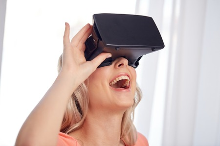 technology, virtual reality, cyberspace, entertainment and people concept - happy amazed young woman with virtual reality headset or 3d glasses at home