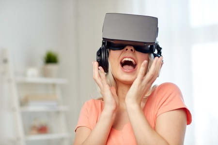 technology, virtual reality, cyberspace, entertainment and people concept - happy amazed young woman in virtual reality headset or 3d glasses and headphones at home Stock Photo