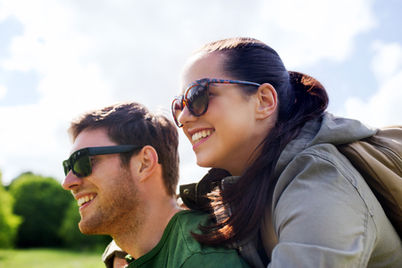 piggy back: travel, hiking, backpacking, tourism and people concept - happy couple in sunglasses with backpacks having fun and hugging outdoors
