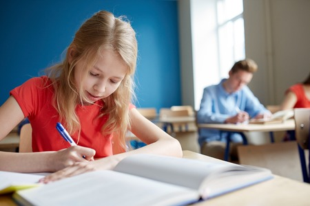 spolužák: education, learning and people concept - student girl with book writing school test