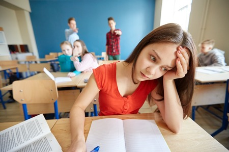 education, bullying, conflict, social relations and people concept - students teasing and judging girl classmate behind her back at school Stockfoto