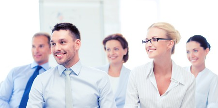 young executive: picture of smiling businessmen and businesswomen on conference