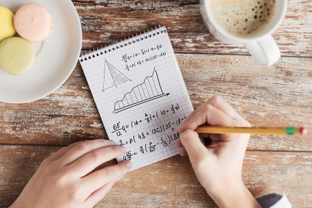 equation: business, education and people concept - close up of female hands with pencil, coffee and cookies solving task or writing mathematical equation to notebook