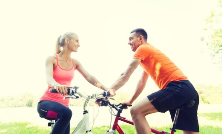 men talking: fitness, sport, people and healthy lifestyle concept - happy couple riding bicycle outdoors at summer