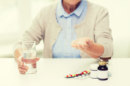 home health care: age, medicine, health care and people concept - close up of senior woman with pills and glass of water at home Stock Photo