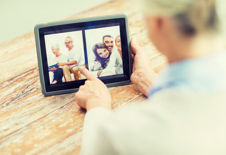 computer age: technology, age, memories and people concept - happy senior woman with tablet pc computer viewing family photo album at home Stock Photo