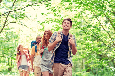 backpacks: adventure, travel, tourism, hike and people concept - group of smiling friends walking with backpacks in woods
