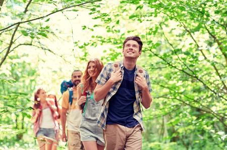 avontuur, reizen, toerisme, wandelen en mensen concept - groep van lachende vrienden lopen met rugzakken in het bos Stockfoto