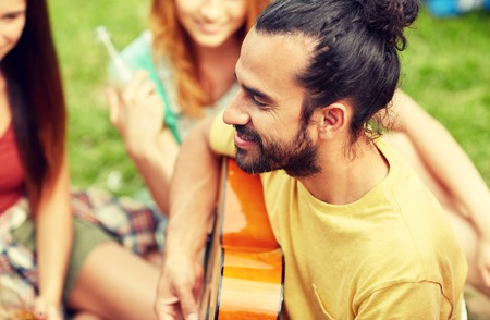 boyfriend: travel, tourism, hike, leisure and people concept - happy man with friends playing guitar at camping