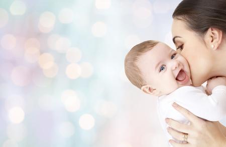 la familia, la maternidad, la paternidad, la gente y el concepto de cuidado de niños - feliz madre que besan al bebé adorable sobre las vacaciones azules fondo de las luces
