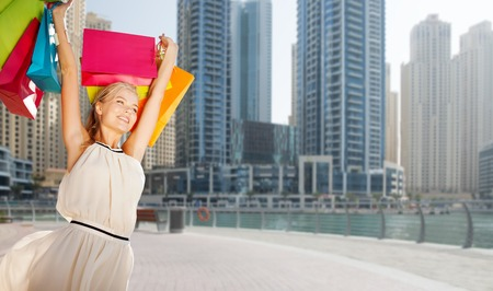 happy shopping: people, holidays, tourism, travel and sale concept - young happy woman with shopping bags over dubai city street background Stock Photo