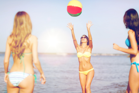 summer holidays, vacation and beach activities concept - girls in bikinies playing ball on the beach