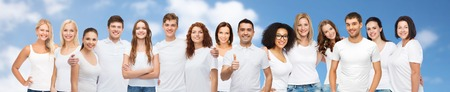 group of men: diverse, gesture and people concept - group of happy different body size and age and gender people in white t-shirts hugging showing thumbs up over blue sky and clouds background Stock Photo
