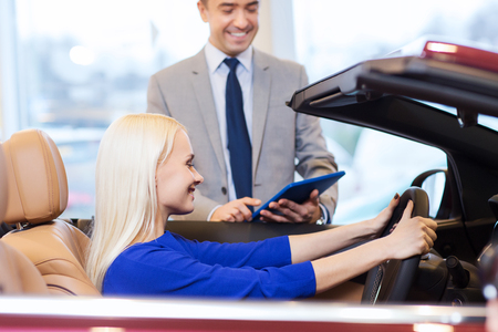 auto business, car sale, technology and people concept - happy woman and car dealer with tablet pc computer in auto show or salon