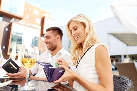 払って財布とワインのグラスと幸せなカップルがレストランで請求日付、人々、関係、支払および財政のコンセプト-
