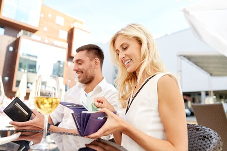 date, people, relations, payment and finances concept - happy couple with wallet and wine glasses paying bill at restaurant
