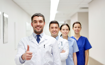 health professionals: profession, people, health care, gesture and medicine concept - group of happy medics or doctors at hospital corridor showing thumbs up