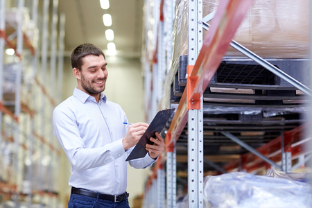 wholesale: wholesale, logistic, business, export and people concept - happy man or manager with clipboard checking goods at warehouse