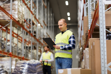 happy workers: wholesale, logistic, people and export concept - man with clipboard in reflective safety vest at warehouse