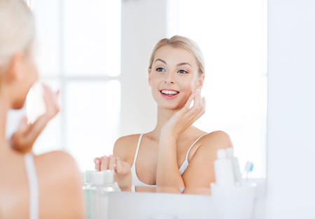 beauty woman: beauty, skin care and people concept - smiling young woman applying cream to face and looking to mirror at home bathroom