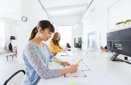 empleado de oficina: negocio, puesta en marcha y la gente concepto - arquitecto asiático o creativo empleado de oficina femenina con regla y dibujo de lápiz en modelo Foto de archivo