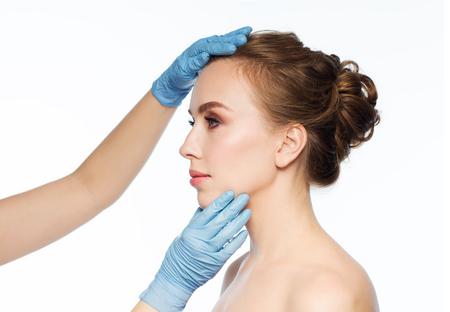 personas, cosmetología, cirugía plástica y el concepto de belleza - las manos del cirujano o esteticista tocar la cara de mujer sobre fondo blanco