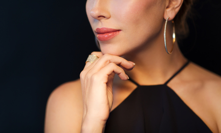 la gente, el lujo, las joyas y el concepto de moda - hermosa mujer en negro que llevaba pendiente del diamante y el anillo sobre fondo oscuro Foto de archivo
