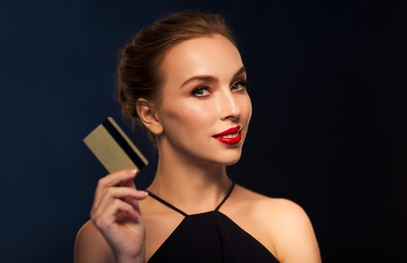 femme fatale: people, luxury, wealth, finances and shopping concept - beautiful woman with credit card over black background