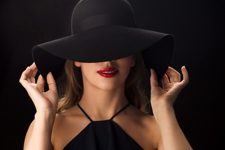 femme fatale: people, luxury and fashion concept - beautiful woman in black hat over dark background Stock Photo