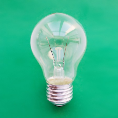 utilization: recycling, energy saving, electricity, environment and ecology concept - close up of lightbulb or incandescent lamp on green