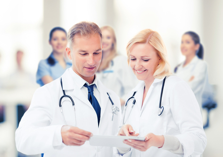 healthcare and technology concept - two doctors looking at tablet pc. Stock Photo