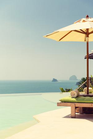Reisen, Urlaub, Tourismus und Luxus-Konzept - schöne Aussicht vom Infinity-Pool mit Sonnenschirm am Meer