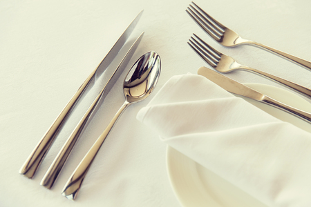 table setting, silverware and eating concept - close up of cutlery set wrapped with napkin and plate on restaurant table Stock Photo