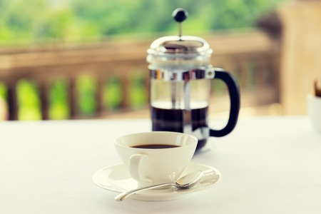 decaf: drinks, energetic, morning and caffeine concept - cup of black coffee and french press on table at restaurant