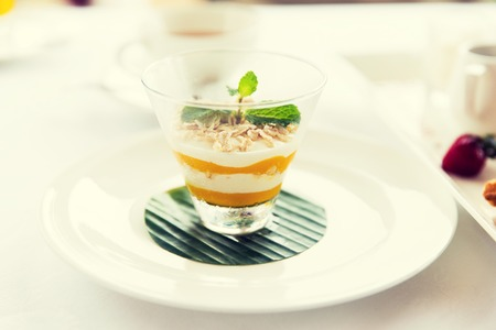 food, dessert, morning, breakfast and eating concept - close up of decorated milk dessert in glass on table at restaurant