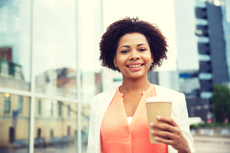 business, drinks and people concept - young smiling african american businesswoman with coffee cup in city
