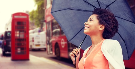 citylife: weather, travel, tourism, citylife and people concept - young smiling african american woman with umbrella over london city street background