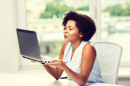 chatting: distant relationship, online communication and love concept - happy young african american woman sending kiss to laptop computer Stock Photo