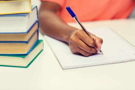 escribiendo: las personas, la tecnología, la educación y el aprendizaje concepto - cerca de African American mujer escrito joven para portátil con libros en el hogar