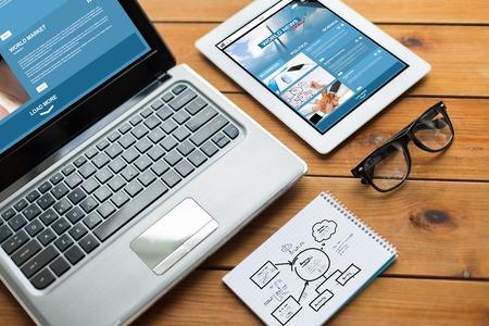 negocio, el diseño y la tecnología sensible concepto - cerca de en el ordenador portátil, PC de la tableta, portátil y anteojos con noticias del mundo y el esquema sobre la mesa de madera Foto de archivo