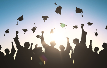 education, graduation and people concept - silhouettes of many happy students in gowns throwing mortarboards in air Stock Photo - 63064200