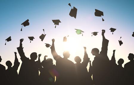 edukacji, nauki i koncepcji osób - sylwetki wielu szczęśliwych studentów w suknie rzucanie Mortarboards w powietrzu Zdjęcie Seryjne